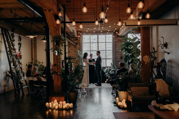 Intimate loft wedding ceremony with string lights