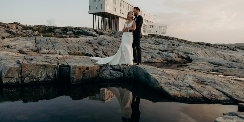 Couple standing on rocks eloping at Fogo Island Inn